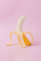 Peeled banana on pink background with copy space