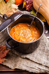 Image of soup puree in saucepan, pumpkin on linen cloth