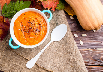 Picture of pumpkin soup in blue cup on linen cloth