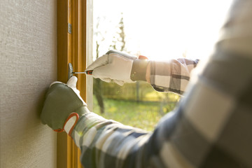 Handyman fixing the window with screwdriver