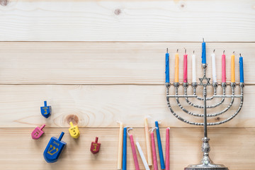 Hanukkah/ Chanukah Jewish holiday background with menorah (Judaism candelabra)  burned candles and traditional Dreidrel game toy on wood table backdrop