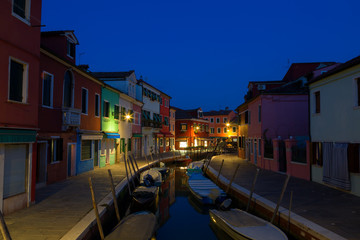 Colorful houses and boats at night in Burano, Venice Italy.