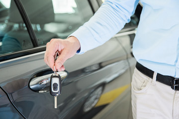 Close up photo of male car dealer hand holding a car key next to a car door. Person is wearing smart casual clothes in beige and blue colors.