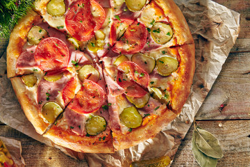 Pizza Restaurant Menu - Delicious Fresh Pizza with Tomato, Ham and Pickled Cucumber. Pizza on Rustic Wooden Table with Ingredients