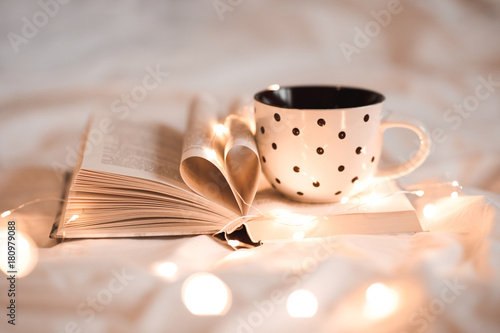 Open book with folded sheets in heart shape and cup of tea in bed