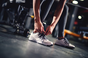 Woman's hand tying shoelaces in the gym near the dumbbells before exercising close up.