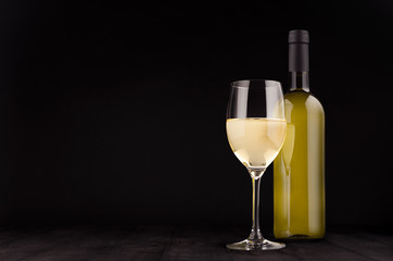 Green bottle of white wine and wine glass mock up on elegant dark black wooden background, copy space.