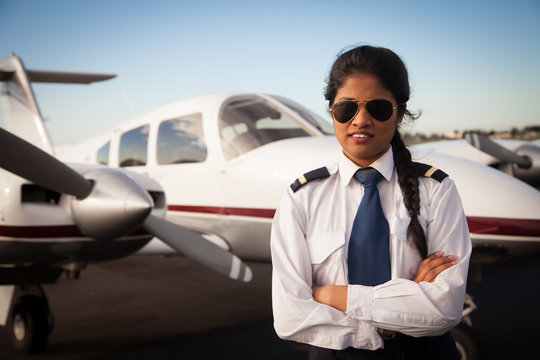 Female Pilot Standing in front of her Aircraft