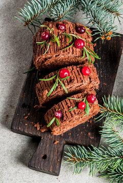 Traditional Christmas dessert, Christmas yule log cake with chocolate cream, cranberry and rosemary twigs. With Christmas tree branches, gifts and decorations, copy space