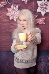 Pretty Slim Blonde Woman With Yellow Cup Of Morning Coffee on The Kitchen Cookies Background