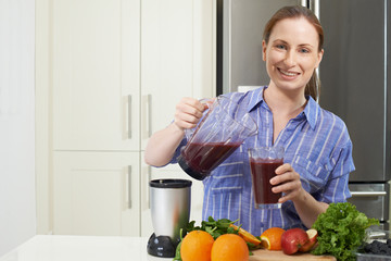Portrait Of Woman Making Juice Or Smoothie In Kitchen