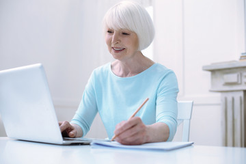 Progressive pensioner. Active progressive cheerful old woman looking happy while working at her laptop