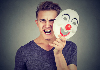 Portrait angry screaming man taking off a clown mask expressing happiness isolated on gray background. Human emotions feelings
