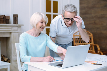 Attentive husband. Responsible smiling old woman looking at the screen of a modern laptop while her caring loving husband standing by her side