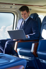 Businessman Working On Laptop In Helicopter Cabin During Flight