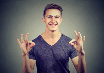 Satisfied happy man gesturing Ok sign isolated on gray background