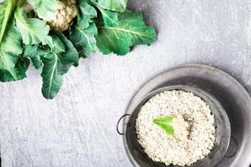 Cauliflower rice in metal bowl on grey background. Top view. Overhead. Copy space. Shredded