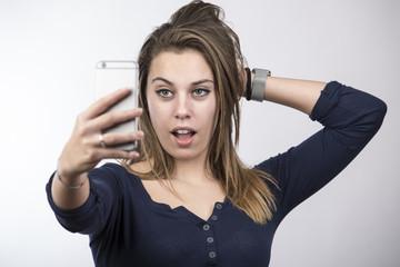 Bella ragazza bionda con vestito blu, si fa un selfie con espressione molto sicura con la bocca aperta - sfondo chiaro