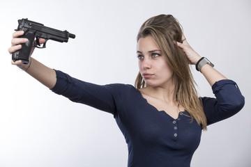 Bella ragazza bionda con vestito blu, si fa un selfie con una pistola - sfondo chiaro