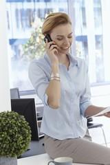 Happy businesswoman talking on mobile