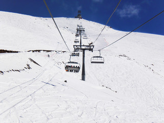 Cableway in the mountains of Dombay. Winter Sunny day