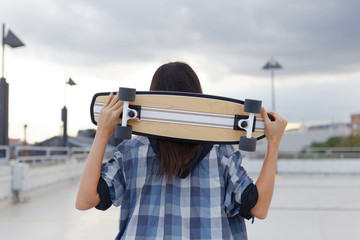 Young hipster woman holding skateboard behind head
