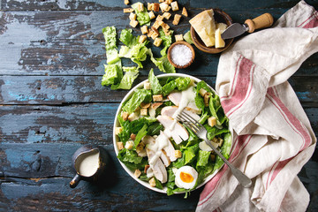 Classic Caesar salad with grilled chicken breast and half of egg in white ceramic plate. Served on towel with ingredients above over old dark blue wooden background. Top view, space. Rustic style