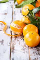 Ripe organic clementines or tangerines with leaves over white wooden plank table as background. Close up, space. Healthy eating