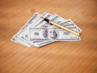 The blurry light design background of Us dollars and pen on wooden desk,