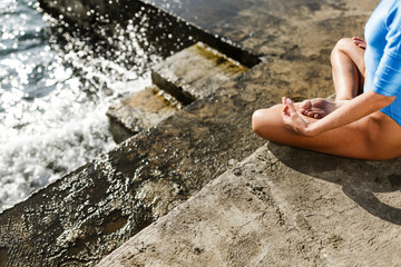 Close up photo of beautiful woman body sitting in lotus pose and meditating by the sea. Photo of woman body in blue swimsuit and waves drops on sea