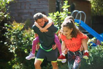Family playing piggyback race in garden