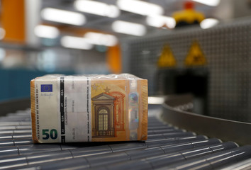Bundles of 50 Euro banknotes move along a conveyer belt at the Money Service Austria company's headquarters in Vienna
