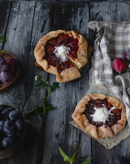 plum crostata pies with ice cream on gray wooden table with textile, fresh plums and herbs