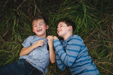 Brothers lying on grass together