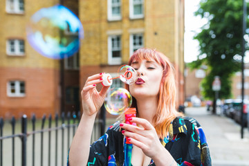 Young woman with dip dyed hair blowing bubbles