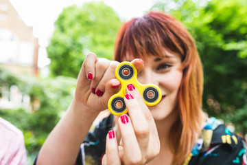 Young woman playing with fidget spinner in park