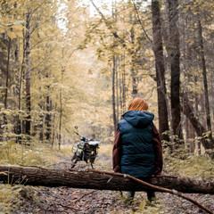 Woman on fallen tree in forest, motorbike in background, Ural, Bashkortostan, Russia