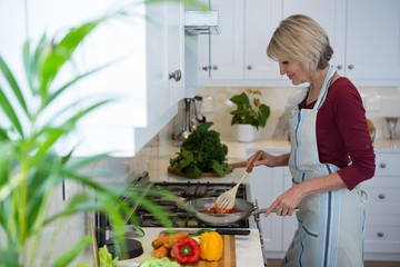 Beautiful woman cooking food in kitchen