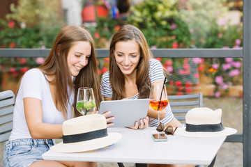 Two young female friends looking at digital tablet at sidewalk cafe