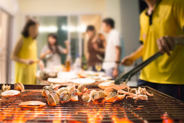 Selective focus on roasted seafood party with blurred background of people