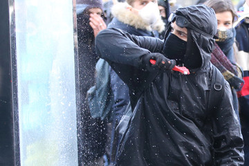 A protestor breaks a window during a demonstration against French government reforms in Nantes