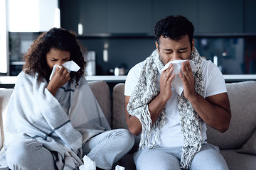 Black man and woman are sitting on the couch. They catch a cold and blow their nose in paper napkins.