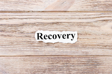 Recovery of the word on paper. concept. Words of Recovery on a wooden background