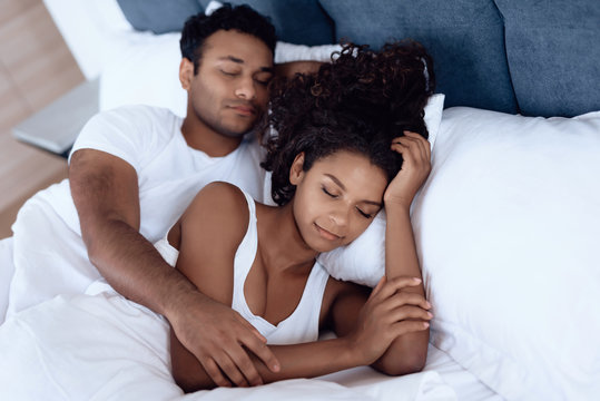 Black man and woman in the bedroom. A woman is lying in bed and her man is hugging her. They sleep embracing each other.