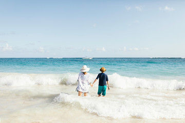 Mother and son, holding hands, standing in surf on beach, rear view