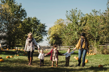 Women and children holding hands in field of pumpkins, Oshawa, Canada, North America