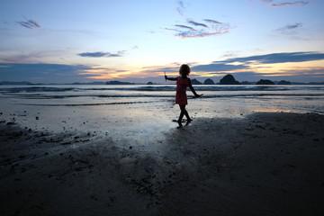 Silhouette of the little girl playing at the sunset shore. Thailand. Krabi. Tubkaek beach