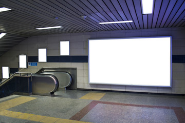 blank billboard beside escalator in subway useful for your advertising