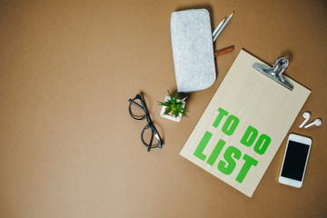 To do list for businessman, phone and headphones on brown office table. Top view, Flat lay. Space for text