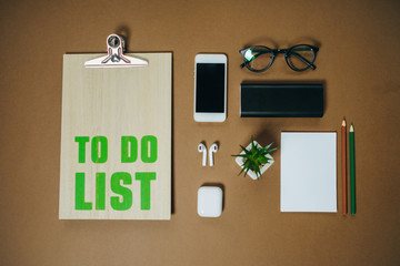 Planning and design concept. To do list for businessman, phone and headphones on brown office table. Top view, Flat lay